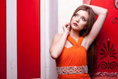 Sensual girl on red vintage wall — Stockfoto
