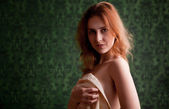 Sexy redhead covering breasts with linens — Stock Photo