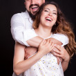 Pregnant woman with her husband laughing over black background — Stock Photo #78776676