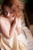 Naked woman in bed covering her self with bed sheets — Stock Photo