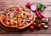 Pizza se šunkou, paprikou a olivami. vynikající čerstvá pizza na dřevěný stůl. — Stock fotografie