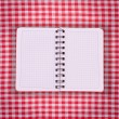 Pure notebook for recording menu, recipe on red checkered tablecloth tartan. — Stock Photo #52142927