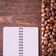 Pure notebook for menu, recipe record on wooden table top view. Coffee beans as background — Stock Photo #52143591