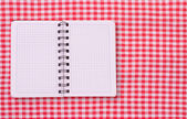 Pure notebook for recording menu, recipe on red checkered tablecloth tartan. — Stock Photo