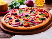 Pizza with ham, pepper and olives. Delicious fresh pizza served on wooden table. — Stock Photo
