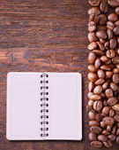 Pure notebook for menu, recipe record on wooden table top view. Coffee beans as background — Stock Photo