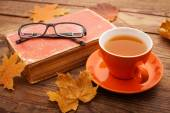 Autumn leaves, book and cup of tea on wooden table in studio — Foto Stock