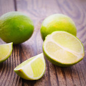 Fresh limes on wooden background. — Stock Photo