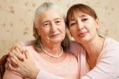 Senior woman with their caregiver at home. — Stock Photo
