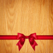 Red ribbon and bow, wooden background — Stock Photo #60156525