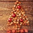 Christmas tree made of hazelnuts with red baubles and gifts — Stock Photo #60156539