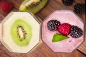 Drink smoothies four summer strawberry, blackberry, kiwi, raspberry on wooden table. — Stock Photo