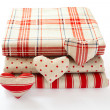 Linen fabric with red polka dots, plaid and stripes for needlework stacked in pile isolated. — Stock Photo #61804049
