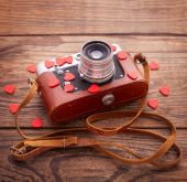 Retro Camera with red hearts on wooden background. — Stock Photo