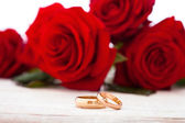 Wedding rings and wedding bouquet of red roses. — Stock Photo