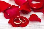 Wedding rings and wedding bouquet of red roses petals. — Stock Photo