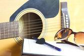 Chitarra da vicino e matita per creare attenzione selezionare musica — Foto Stock