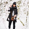 Smiling brunette woman in winter forest — Stock Photo #65050975