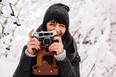 Smiling girl photographed on a camera in winter forest — Foto Stock