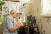 Retired man working at home on his handicrafts — Stock Photo