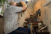 Senior man working at a workbench — Stock Photo