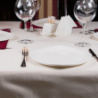 Empty white plate in a formal table setting — Stock Photo #55007237