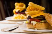 Gourmet Cheeseburgers Piled High with Toppings — Stock Photo