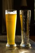 Glass of Beer Beside Empty Glass on Table — Stock Photo