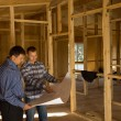 Two builders discussing the interior of a house — Stock Photo #56492557