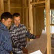 Two builders inside a half completed house — Stock Photo #56492573
