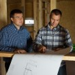 Two builders checking a blueprint together — Stock Photo #56492637