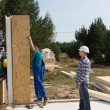 Builders erecting insulated wall panels — Stock Photo #56492885