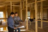 Two builders discussing the interior of a house — Stock Photo