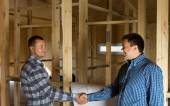 Two men shaking hands in a half constructed house — Stock Photo