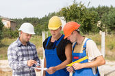 Architect and builders discussing specifications — Stock Photo