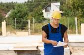 Builders checking specs or an order — Stockfoto