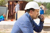 Builder enjoying a cup of coffee on site — Stockfoto