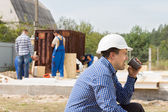 Workman drinking coffee on a building site — Stockfoto