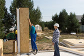 Builders erecting insulated wall panels — Stock Photo