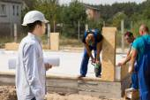 Young architect watching construction workers — Stock Photo