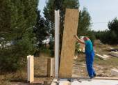 Worker erecting wall panels on a building site — Stock Photo