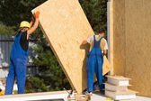 Construction workers positioning wall panels — Stock Photo