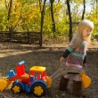 Little girl with a toy construction vehicle — Stock Photo #57398325
