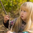 Little blond girl playing with a wooden branch — Stock Photo #57398407