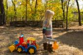 Little girl with a large colorful plastic tractor — Stock Photo