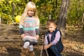 Young boy and girl playing outdoors in woodland — Foto de Stock