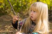 Little blond girl playing with a wooden branch — Stock Photo