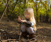 Girl Building Stick Structure Outdoors in Autumn — Stock Photo