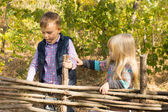 Two young children playing at a wooden fence — Stock Photo