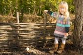 Stylish little girl next to a rustic wooden fence — Stock Photo